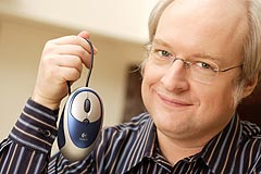 Photograph of Jakob Nielsen holding a mouse.